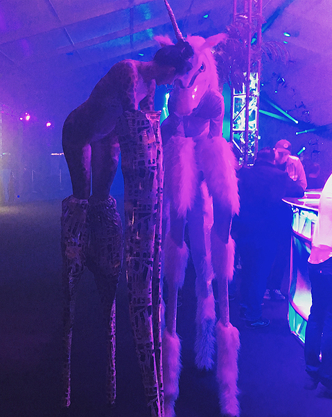 Inventive stilt walkers a giraffe and a unicorn graze freely