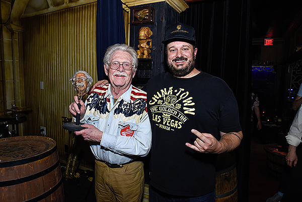 Lonnie Hammargren strikes a pose with his shrunken head and The Golden Tikis Managing Partner Branden Powers