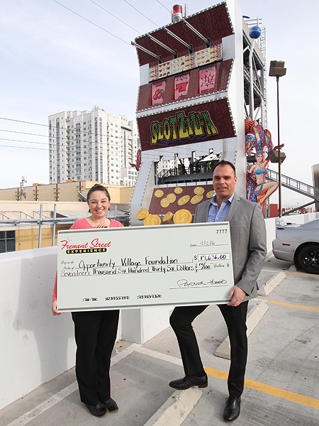 From left to right: Veronica Atkins, Special Events Manager at Opportunity Village; Paul McGuire, Chief Marketing Officer for Fremont Street Experience. Fremont Street Experience presents a check for $17,636 to Opportunity Village. The proceeds were raised from SlotZilla revenue on Dec. 3, 2016 from 10 a.m. – 5 p.m. Photo courtesy of Scott Roeben of Fremont Street Experience.