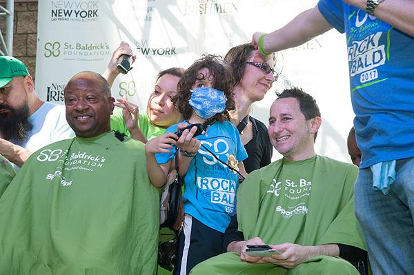 Cancer patient Elan Saula and mother Leslie Saula shave family friend Mark Gardberg during St. Baldricks Day event at New York New York Hotel casino